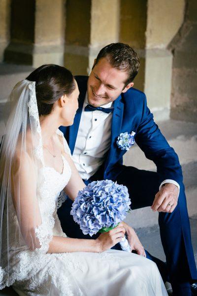 Brautpaar sitzt auf Treppe in Kreuzgang und wird von Hochzeitsfotograf in Trier fotografiert.
