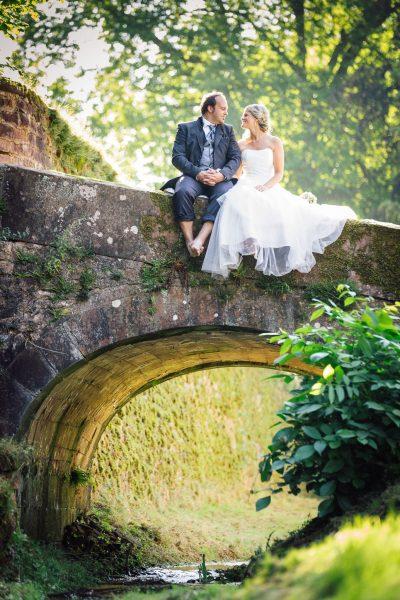 Brautpaar sitzt barfuß auf Brücke über Bach in Schloss Föhren bei Trier.