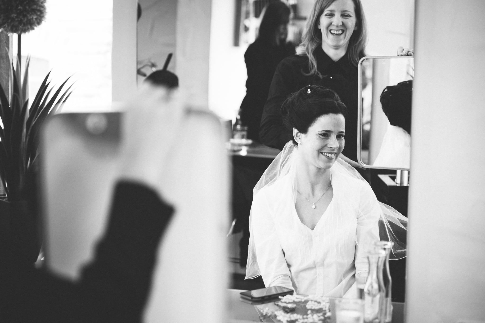 Braut sitzt bei Friseur während Getting Ready